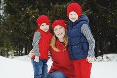 在雪森林里照顾和她的两个儿子获得乐趣在冬天 免版税图库摄影