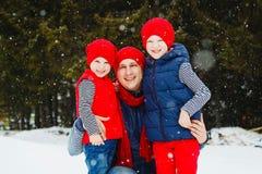 在雪森林里生和他的两个儿子获得乐趣在冬天 免版税库存图片