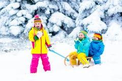 在雪橇乘驾的孩子 飞奔通过雪 冬天雪乐趣 免版税库存图片