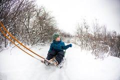 在雪橇的孩子 库存照片