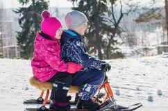 在雪滑行车的儿童乘驾 免版税图库摄影