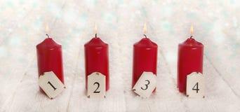 在雪白色木背景的四个红色灼烧的出现蜡烛 库存照片
