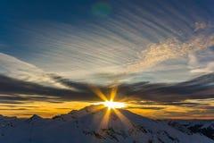 在雪白色高山山的日落 库存照片