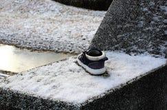 在雪的一双失去的鞋子 免版税库存图片