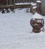 在雪的一台老木燃烧器 免版税库存图片