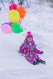 在雪的一套五颜六色的衣服的小女孩在有色的球的冬天森林里 库存照片