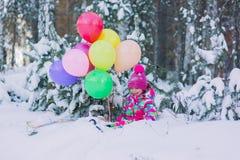 在雪的一套五颜六色的衣服的小女孩在有色的球的冬天森林里 免版税库存照片