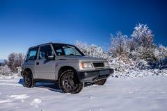 在雪的一辆老越野汽车 免版税库存照片