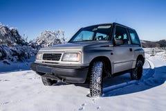 在雪的一辆老越野汽车 免版税库存图片