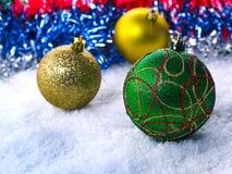 在雪的三个圣诞节球 在前面球的焦点 免版税图库摄影
