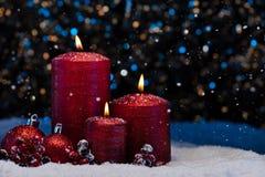 在雪的三个红色蜡烛 免版税库存照片