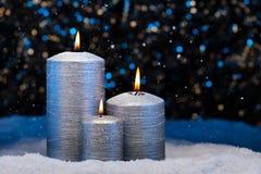 在雪的三个银色蜡烛 免版税库存图片