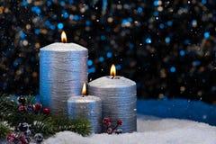 在雪的三个银色蜡烛 免版税库存照片