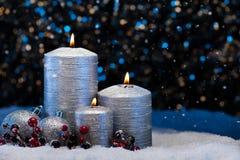 在雪的三个银色蜡烛 库存图片