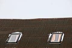 在雪的两个窗口在反对天空的石板屋顶 库存图片