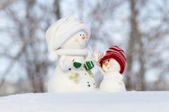 在雪的两个雪人和看看彼此 库存照片