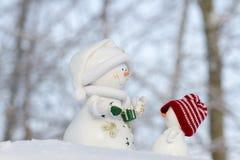 在雪的两个雪人和看看彼此 图库摄影