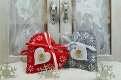 在雪的两心脏在窗口下 圣诞节魔术 免版税库存照片