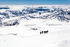 在雪的人上升的剪影在山 免版税图库摄影