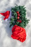 在雪的传统圣诞节标志 圣诞老人的袋子和帽子、圣诞节花圈和装饰的圣诞树 免版税库存照片