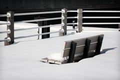 在雪的公园长椅 库存图片