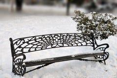 在雪的公园长椅 库存照片