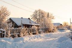 在雪的冬天农村路和结构树 库存图片