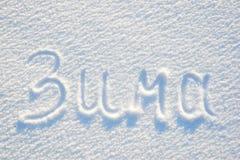 在雪的冬天文本书面俄语纹理或背景的-寒假概念 晴天,与美洲河鲱的明亮的光 库存图片