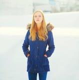 在雪的冬天时尚妇女佩带的夹克 免版税库存照片