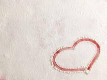 在雪的华伦泰爱红色心脏形状在红色背景 免版税图库摄影