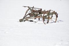 在雪的古板的耕犁 库存图片