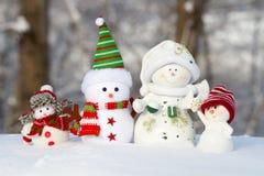 在雪的四个雪人在一行站立 免版税库存照片