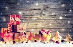 在雪的土气礼物盒与圣诞节装饰品 免版税库存图片