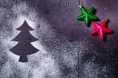 在雪的圣诞树剪影在与红色和绿色星的黑背景 节假日概念 库存图片