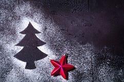 在雪的圣诞树剪影在与红色星的黑背景 节假日概念 库存照片