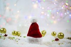 在雪的圣诞老人帽子,与星的闪烁的背景 免版税库存照片