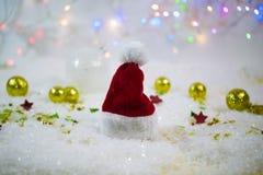 在雪的圣诞老人帽子,与星的闪烁的背景 免版税库存图片