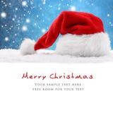 在雪的圣诞老人帽子 免版税库存照片
