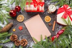 在雪的圣诞节冷杉木与锥体、茴香星、肉桂条、葡萄酒时钟、装饰星、圣诞节球和giftbo 免版税库存照片