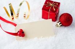 在雪的圣诞节标签与装饰品 免版税库存照片