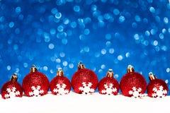在雪的圣诞节红色球在蓝色闪烁 免版税库存图片