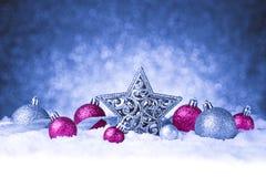 在雪的圣诞节装饰品在闪烁背景 免版税图库摄影