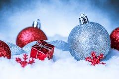 在雪的圣诞节装饰品在闪烁背景 免版税库存图片