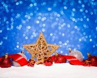 在雪的圣诞节装饰品在闪烁背景 免版税库存照片