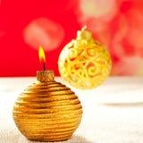 在雪的圣诞节金黄蜡烛和中看不中用的物品 免版税库存图片