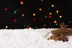 在雪的圣诞节香料与在背景的光 复制空间 免版税库存照片