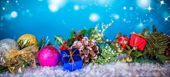 在雪的圣诞装饰在蓝色背景下 库存图片