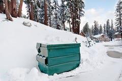 在雪的大型垃圾桶 库存照片