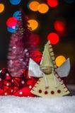 在雪的天使以被弄脏的树和欢乐照明为背景 免版税库存照片