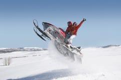 在雪的夫妇跳跃的雪上电车 免版税库存图片